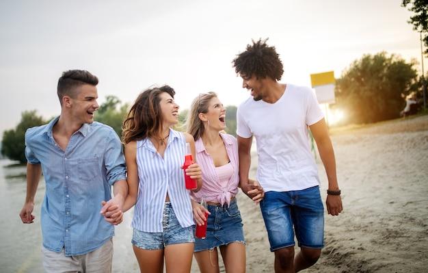 Groep vrienden die plezier hebben op het strand. zomervakantie, vakantie en mensen concept.