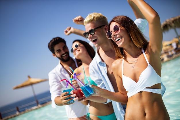Groep vrienden die plezier hebben op zomervakantie en cocktails drinken. jeugd levensstijl, vriendschap, reizen en vakantie concept