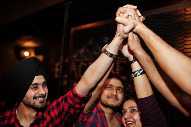 Groep vrienden die pret en rust hebben bij nachtclub en samen high five geven