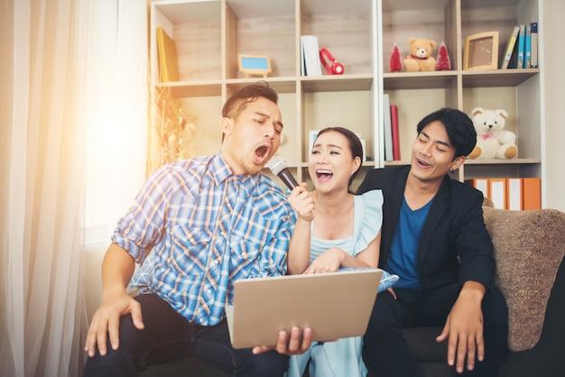 Groep vrienden die pret hebben bij woonkamer die een lied samen zingen