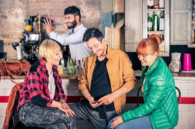 Groep vrienden die pret hebben die smartphone gebruiken bij het restaurant van de hipstercocktailbar