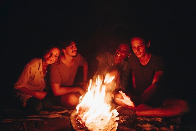Groep vrienden die rond een vuur op een kampeerterrein zitten