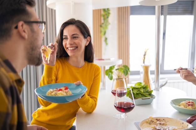 Groep vrienden die samen deegwaren in de keuken eten