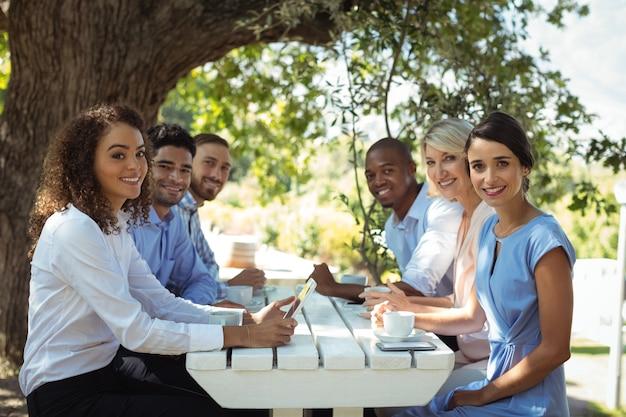 Groep vrienden die samen in openluchtrestaurant zitten
