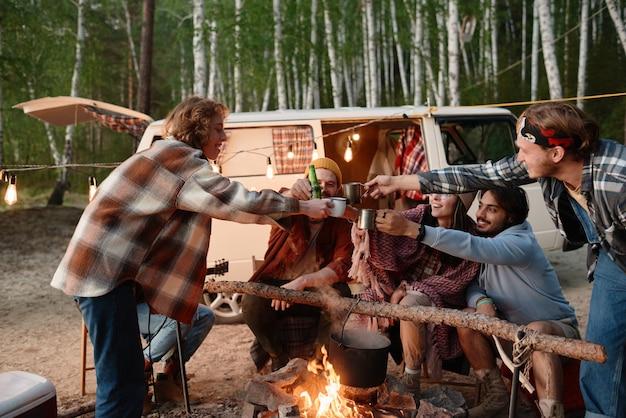 Groep vrienden die samen met een drankje bij het vuur roosteren tijdens het kamperen in het bos