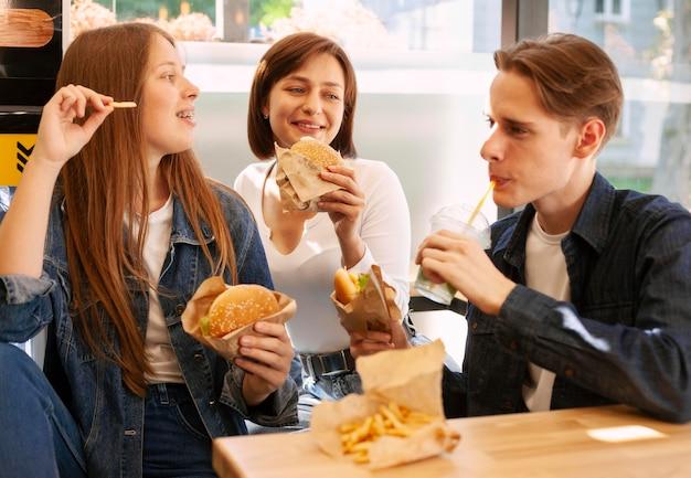 Groep vrienden die samen snel voedsel eten