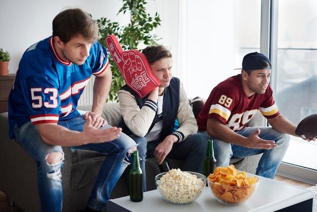 Groep vrienden die samen voetbalteam steunen