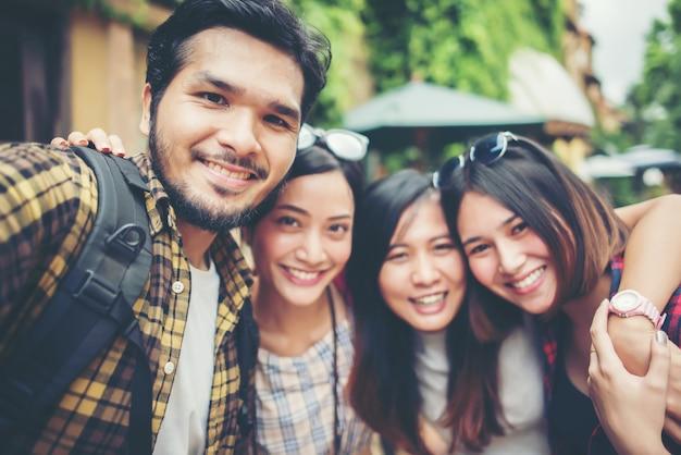 Groep vrienden die selfie in een stedelijke straat nemen die goede pret hebben samen.