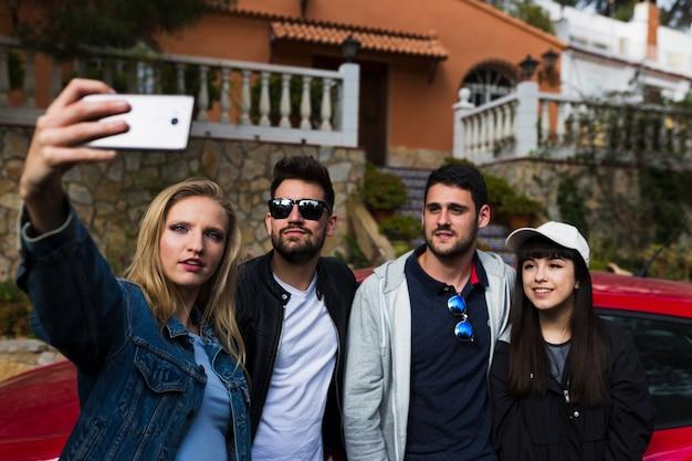 Groep vrienden die selfie met mobiele telefoon nemen