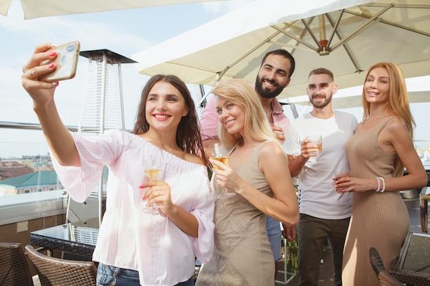 Groep vrienden die selfies op een slimme telefoon samen nemen tijdens feest op het dak