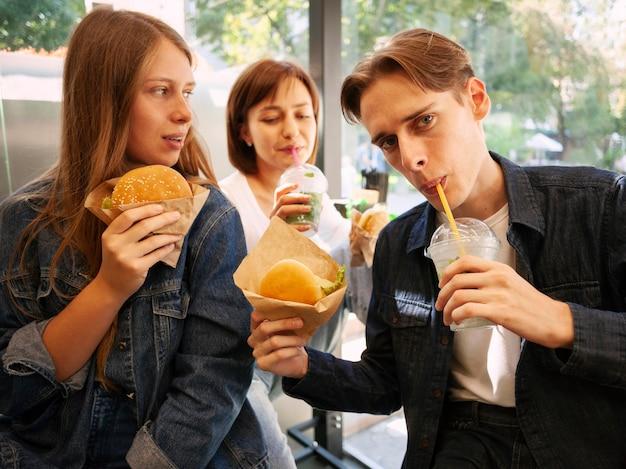 Groep vrienden die snel voedsel eten