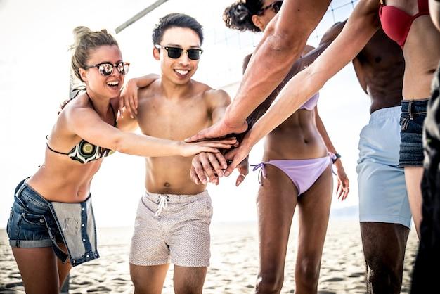 Groep vrienden die strandvolleybal op het strand spelen.