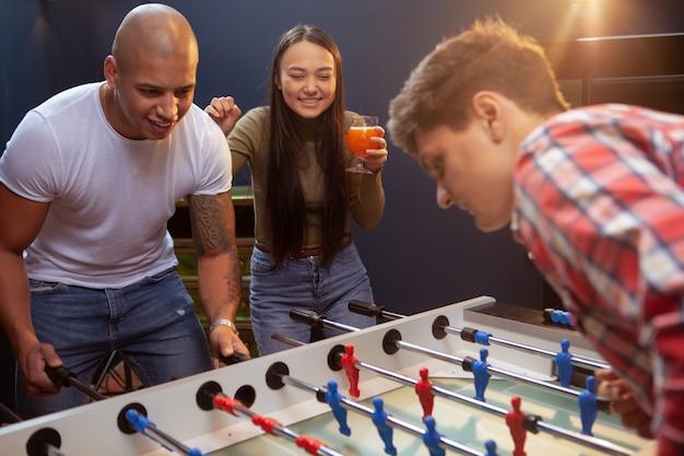 Groep vrienden die tafelvoetbal spelen bij bierbar