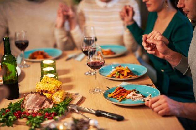 Groep vrienden die thuis bidden boven thanksgiving-kersttafel