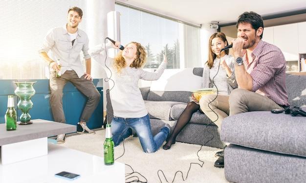 Groep vrienden die thuis karaoke spelen