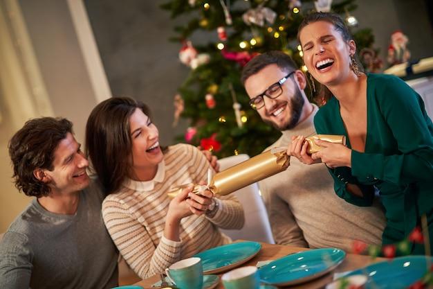 Groep vrienden die thuis kerstcrackers trekken