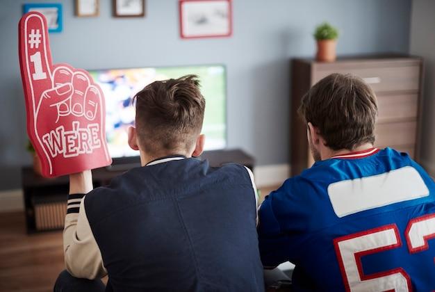 Groep vrienden die thuis voetbal kijken
