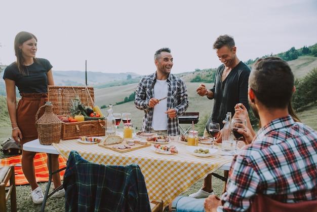 Groep vrienden die tijd doorbrengen die een picknick en een barbecue maken