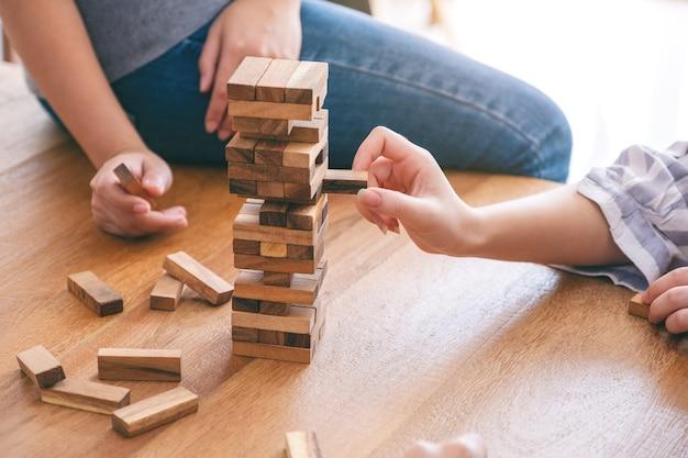 Groep vrienden die tumble tower houten blokspel zitten en spelen samen met een gelukkig gevoel