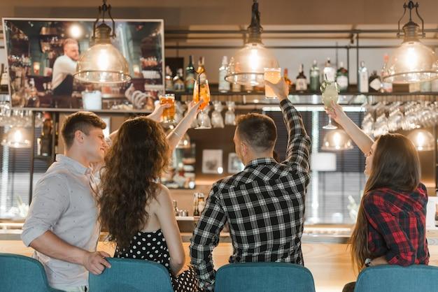 Groep vrienden die van dranken in bar genieten