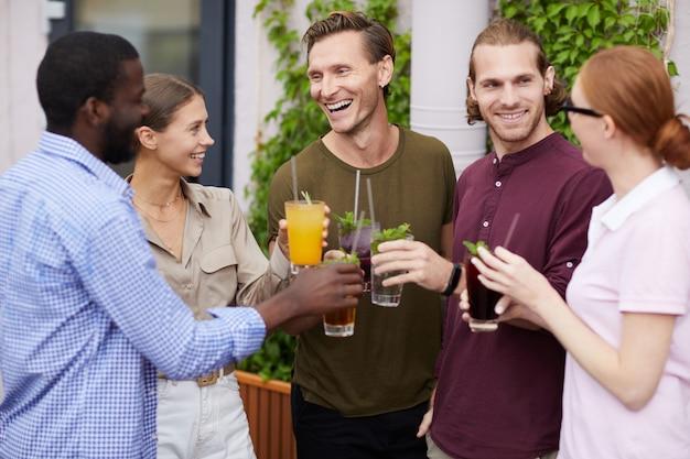 Groep vrienden die van drankjes in openlucht genieten bij partij