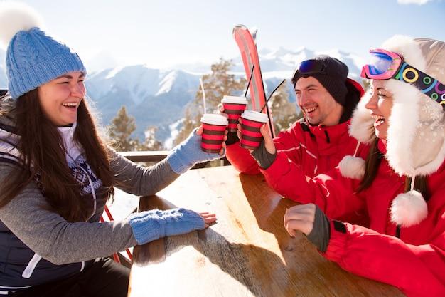 Groep vrienden die van hete thee of koffie in koffie bij skitoevlucht genieten
