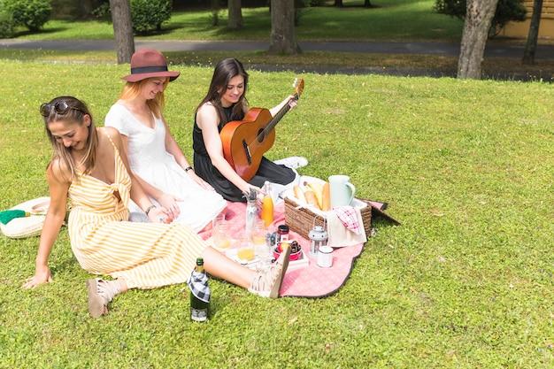 Groep vrienden die van snack genieten bij picknick