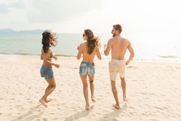 Groep vrienden die van zomer genieten bij het strand