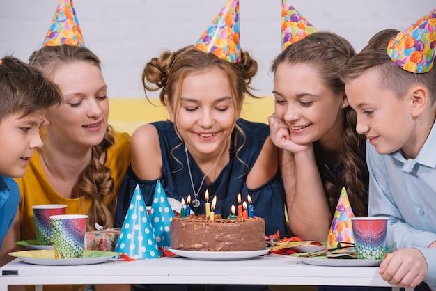 Groep vrienden die verjaardagscake bekijken die met kaarsen wordt aangestoken