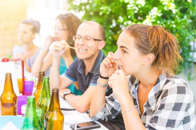 Groep vrienden die vleesvleespennen eten