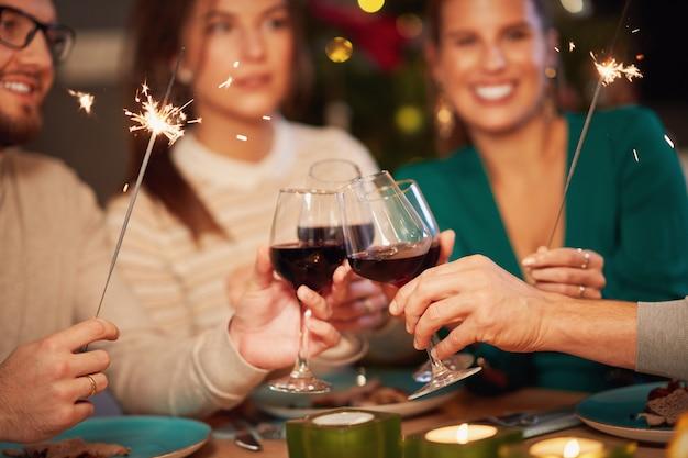 Groep vrienden die wijn drinken en thuis kerstmis vieren
