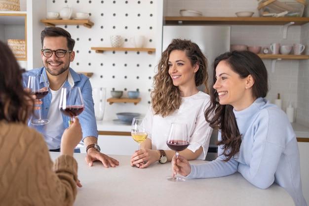Groep vrienden die wijn drinken in de keuken