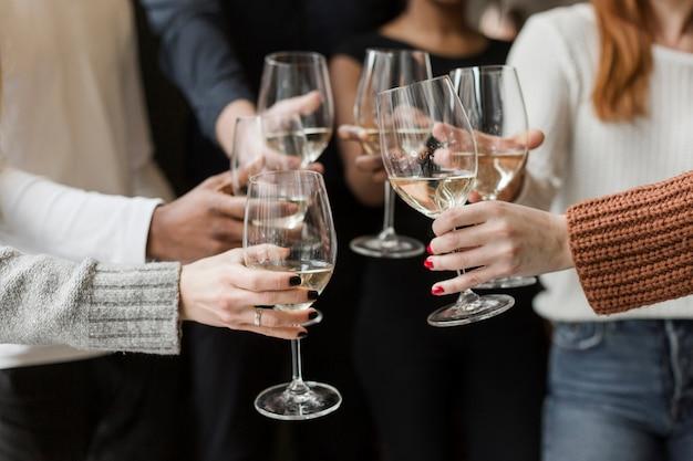 Groep vrienden die wijnglazen samen roosteren