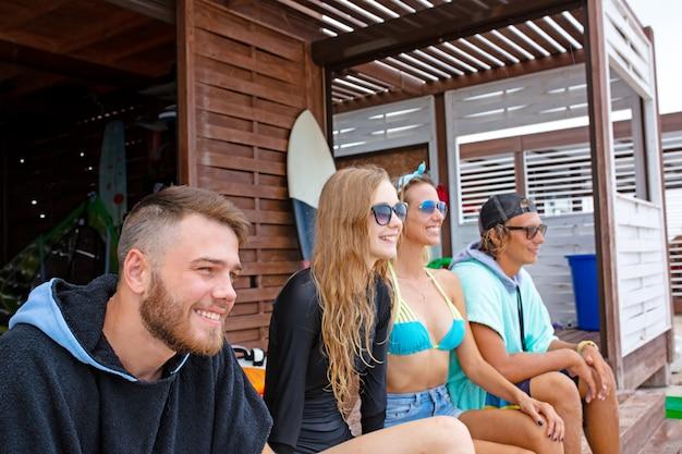 Groep vrienden die zwembroekzitting met surfplanken op strand dragen