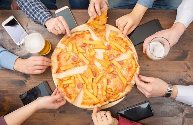 Groep vrienden drinken bier, eten pizza, praten en glimlachen terwijl ze thuis rusten