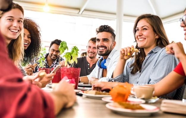 Groep vrienden drinken cappuccino in koffiebar-restaurant - mensen praten en plezier samen op mode cafetaria - vriendschap concept met gelukkige mannen en vrouwen in café