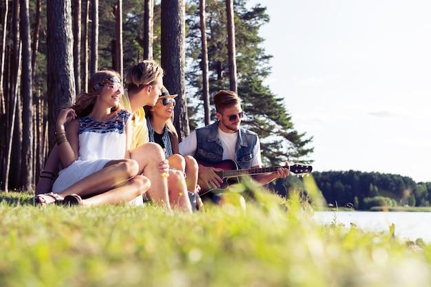 Groep vrienden feesten en luisteren naar muziek bij zonsondergang.