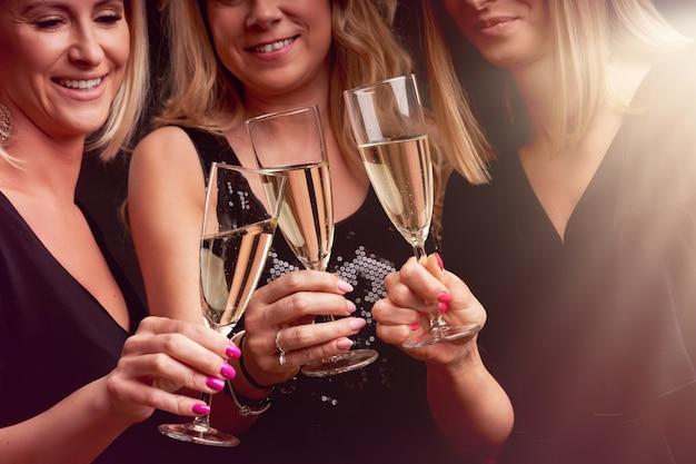 Groep vrienden feesten in een nachtclub en toasten op drankjes