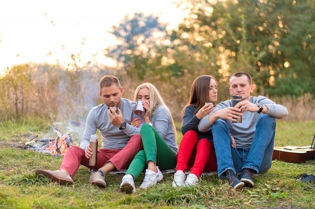 Groep vrienden geniet van een warm drankje uit een thermosfles, op een koele avond bij een vuur in het bos. leuke tijd kamperen met vrienden