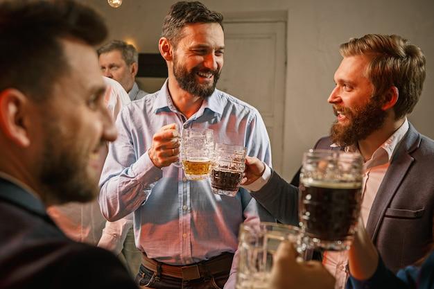 Groep vrienden genieten van avonddrankjes met bier
