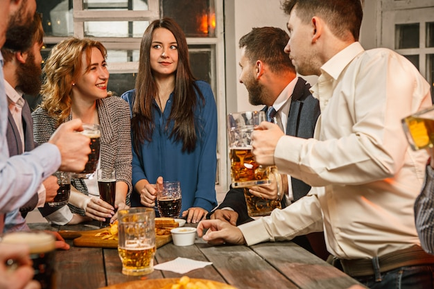 Groep vrienden genieten van drankjes in de avond met bier