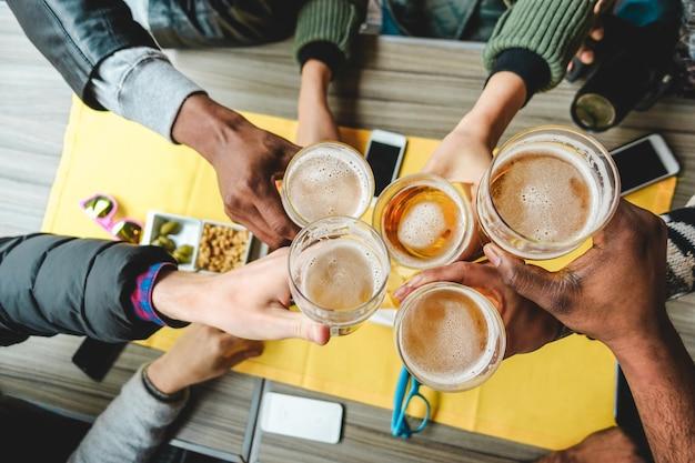 Groep vrienden genieten van een bierglazen in engels pubrestaurant. jonge mensen juichen op vintage bar