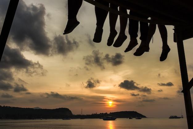 Groep vrienden genieten van een warme zonsondergang zittend op het dok van de baai op het eiland koh samui, thailand. silhouetten van mensenbenen bij openhartige schemering aan zee. ontspan, ontspan concept