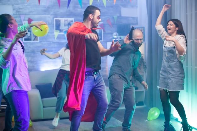 Groep vrienden genieten van hun tijd op een feest in een kamer met neonlichten. man in superheld kostuum.