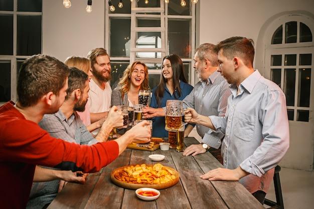 Groep vrienden genieten van 's avonds drankjes met bier op houten tafel