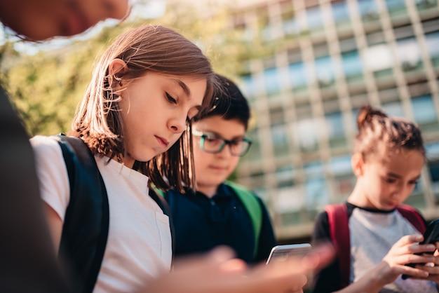 Groep vrienden hangen rond na school en het gebruiken van slimme telefoon