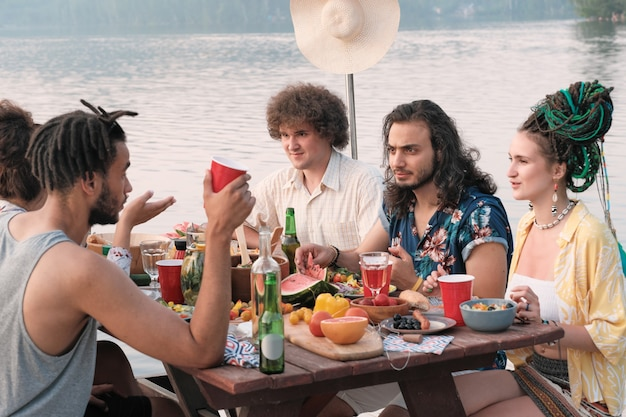Groep vrienden hebben een picknick over de natuur, ze zitten aan de eettafel, eten, drinken en praten
