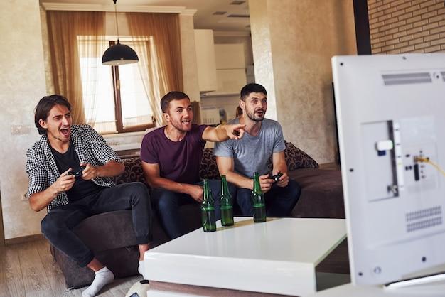 Groep vrienden hebben plezier met het spelen van consolegames binnenshuis in de woonkamer.