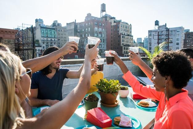 Groep vrienden in afwachting van tijd samen op een dak in de stad van new york, levensstijlconcept met gelukkige mensen