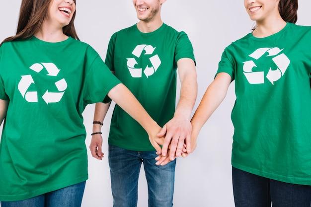 Groep vrienden in groene t-shirt die hun handen stapelt